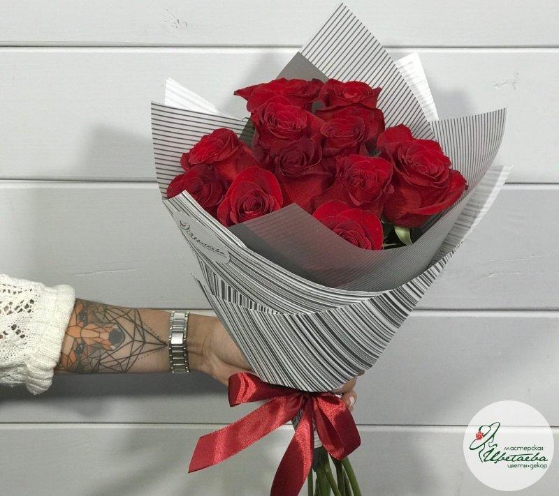 Букет из 11 красных роз в руках девушки вид сбоку